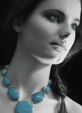 A lady wearing a turquoise necklace