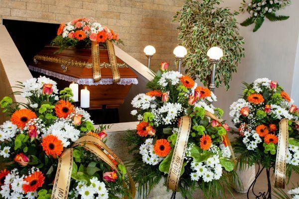 delle composizioni di fiori con dei nastri e una bara in legno