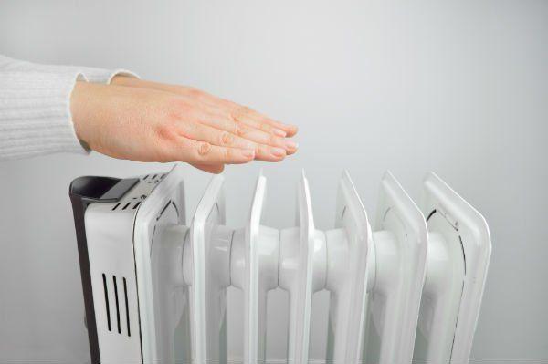 due mani vicino a un calorifero