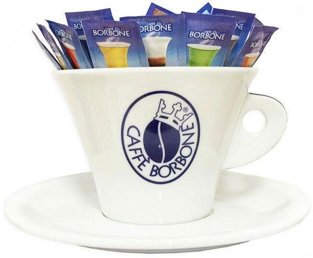 una tazza con scritto Caffe' Borbone e dentro delle bustine di zucchero