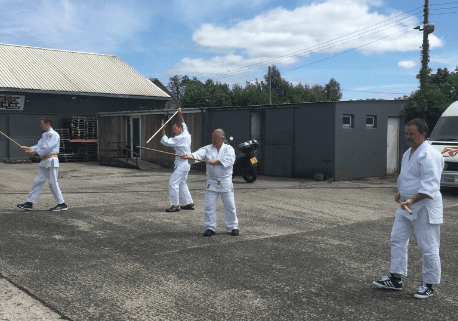 Aikido students practicing the jo outside