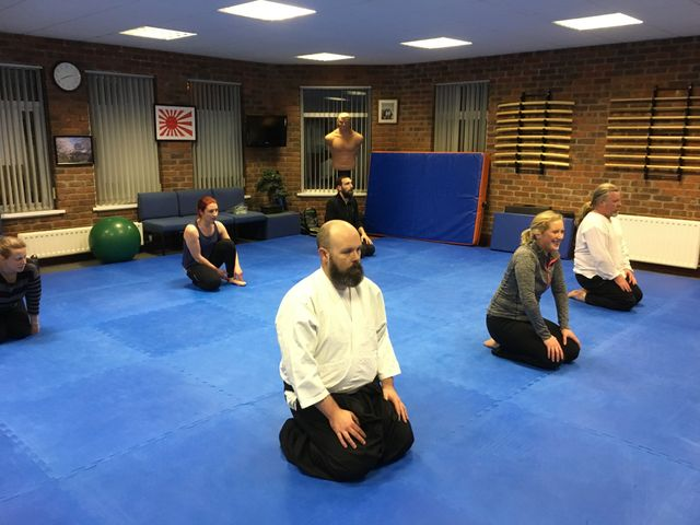 Male and female students kneeling at end of lesson at Matin Acton's Aikido  Institute