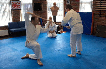 Two aikido students doing a throw with a wooden staff