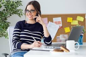 This is a woman smiling, working at her desk & talking on the phone