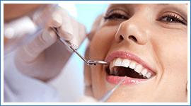 Dentista usa specillo e specchietto su una ragazza sorridente