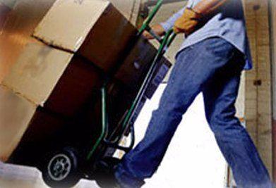 un uomo con un carrello con degli scatoloni