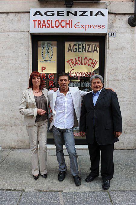 due uomini e una donna davanti all' Agenzia Traslochi Express