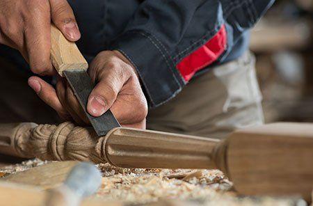 due mani che lavorano del legno con una lima