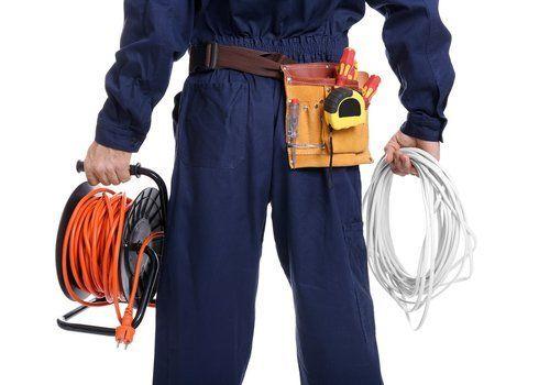 elettricista con tuta da lavoro e attrezzi in mano e nel marsupio