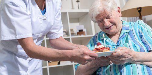 infermiera che da un piatto con un dolce ad un anziano