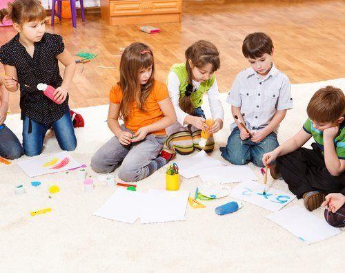 bambini mentre disegnano per terra