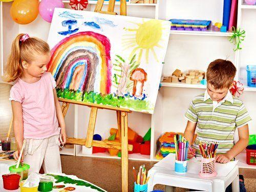 bambino mentre disegna e una bambina guarda il suo lavoro