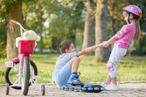 bambina aiuta un bambino ad alzarsi sui pattini