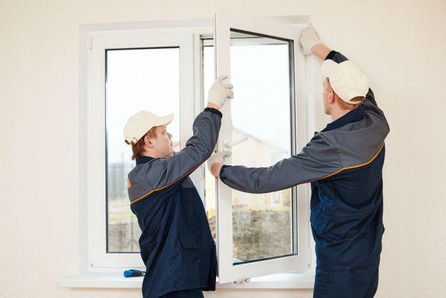 due uomini che installano una finestra di PVC
