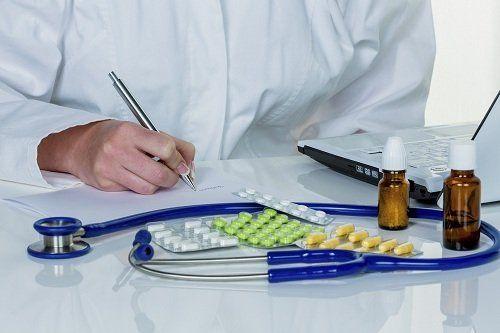 medico al computer con farmaci e stetoscopio sul tavolo
