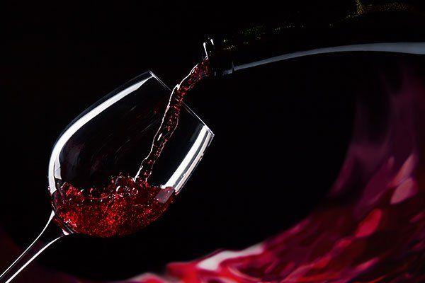 Riempiendo un bicchiere di vino rosso dove si apprezza il colore