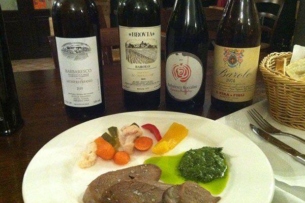 Carni alla lastra con salsa di pesto,vegetali cotti,un paniere di pane e quattro bottiglie di vino per scegliere