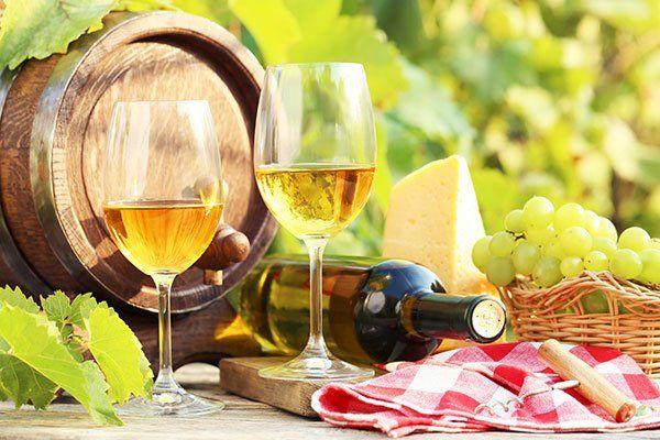 Un piccolo barile, grappoli di uva verde,bicchieri di vino bianco e una bottiglia