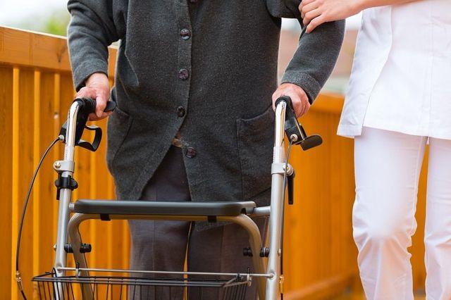 anziano con deambulatore assistito dal personale