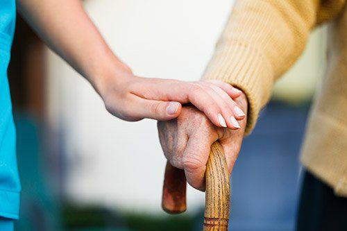 personale tocca la mano di una persona anziana con la zanetta