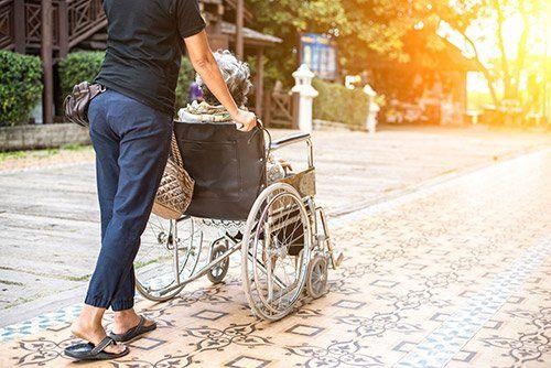 assistente spinge sedia a rotelle di una persona anziana