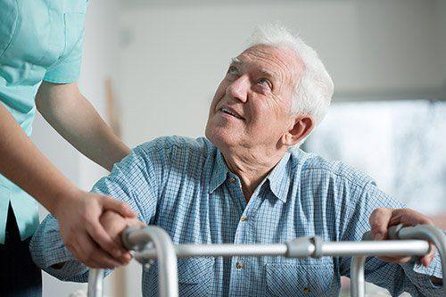 Medico assiste un anziano con il deambulatore