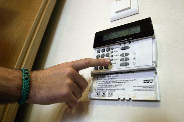 mano preme il codice di accesso di un sistema di sicurezza