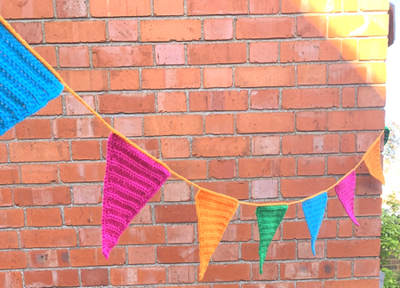 Colorful triangular bunting hanging outside in front of a brick building.