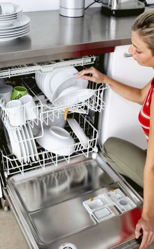 Woman loading dish washer after appliance repair in Hamilton