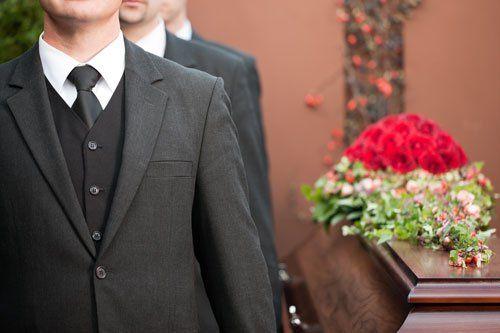 uomini in giacca e cravatta ad un funerale