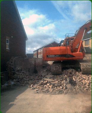 Digger on top of fallen bricks