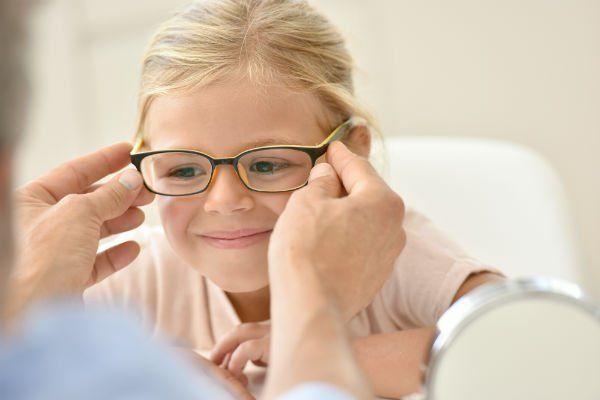 due mani che mettono degli occhiali da vista a una bambina