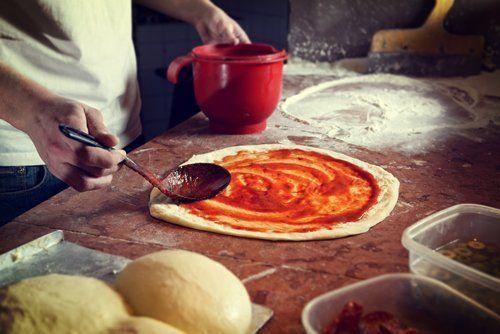 Pizzaiolo mentre prepara una pizza