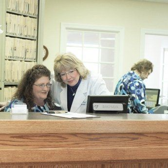 dentist and receptionist looking at paperwork together