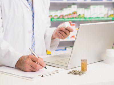 farmacista mentre scrive su un foglio con una scatola di medicinali in mano