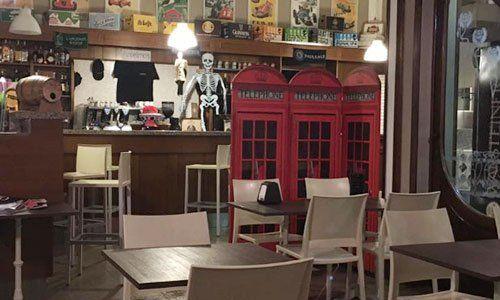 interno della pizzeria con vista dei tavoli e di un rilievo a forma di cabine del telefono inglesi di color rosso