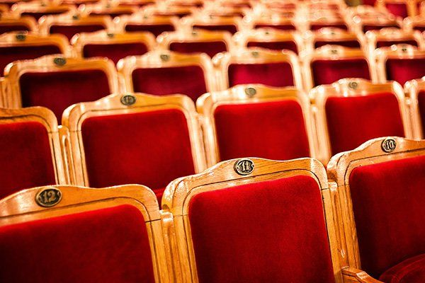 dei posti a sedere con sedie in legno e velluto di color rosso