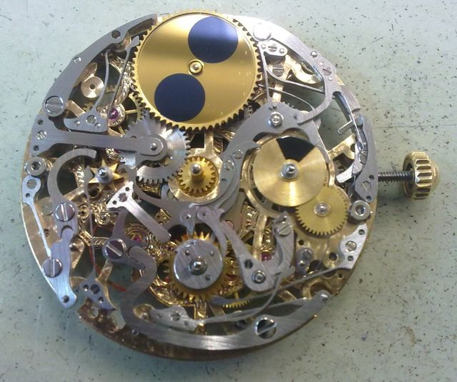 A watch with its back removed, showing its mechanisms