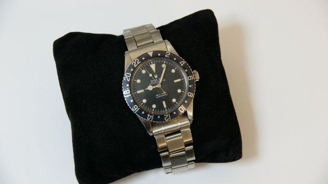 A chrome watch with black face, around a black cushion