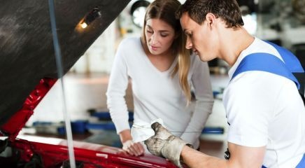 A mechanic looks under the hood with a client