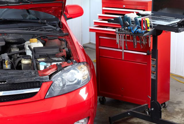 A car has its hood propped open, and tools are set out to begin