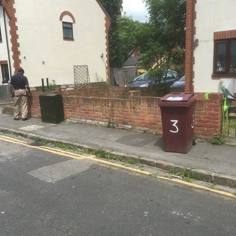 dustbins on the side of a footpath
