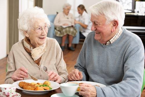 Coppia di anziani felice per l'assistenza anziani mangia cibo in provincia di Caltanissetta