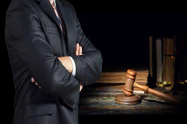 Uomo in piedi con le mani in mano, al suo fianco diversi libri, la bilancia e la maza della giustizia