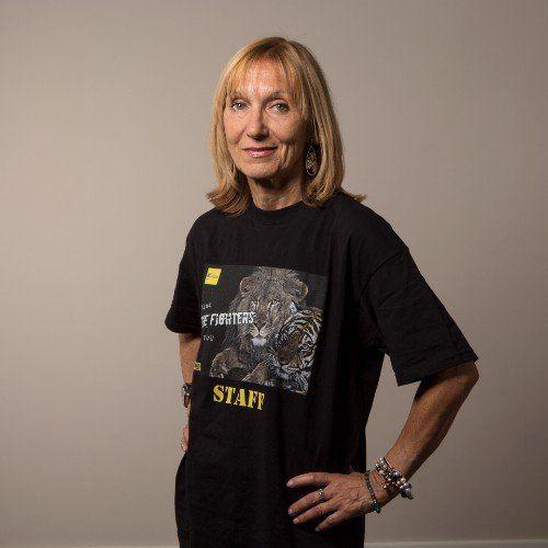 una donna bionda con una maglietta nera con scritto  The Fighters Staff