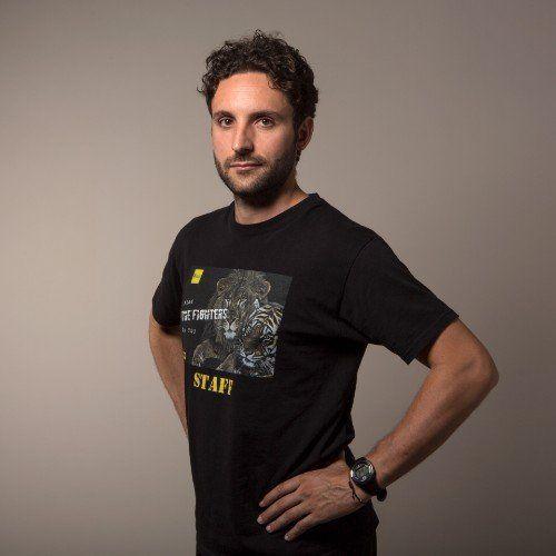 un ragazzo con una t shirt nera con scritto Staff