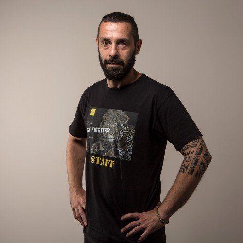 un uomo con la barba, le mani sui fianchi e una t shirt nera con scritto The Fighters Staff
