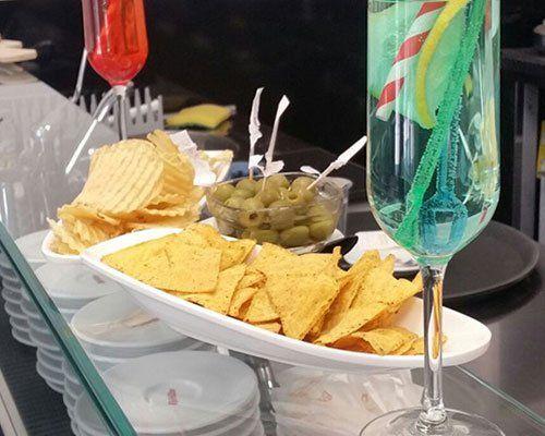 delle patatine, delle olive e due cocktail