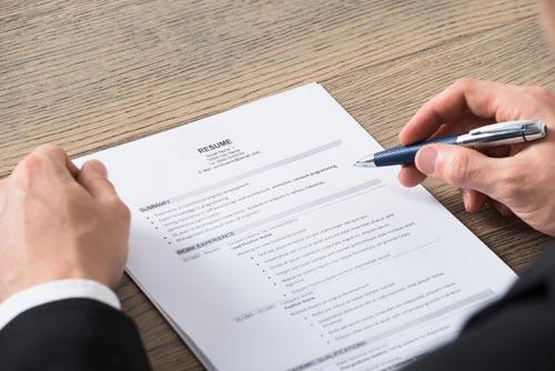 uomo vestito in abito formale consulta un documento con una biro in mano