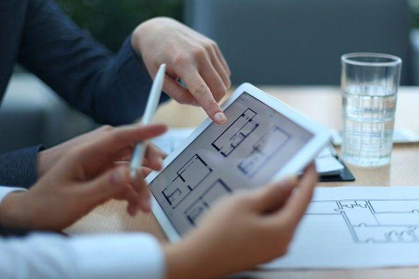 due mani con un tablet e un dito che indica lo schermo